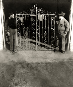 Father & son with wrought iron gate